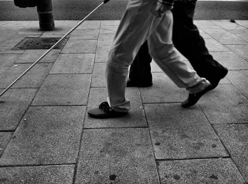 Personne malvoyante qui marche sur un trottoir avec une canne d'aveugle
