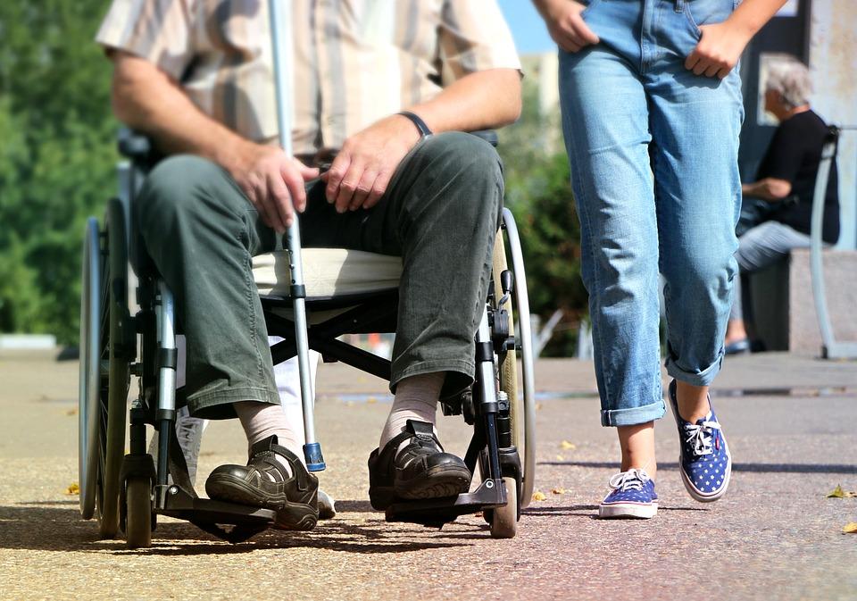 Personne en fauteuil roulant qui se déplace sur un trottoir