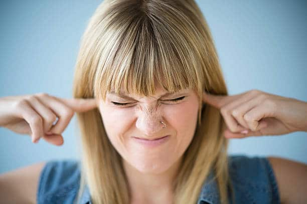 Jeune femme qui se bouche les oreilles pour se protéger des nuisances sonores et du bruit
