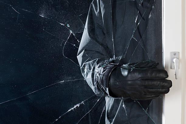 Personne avec main gantée qui a brisé le verre d'une porte d'entrée