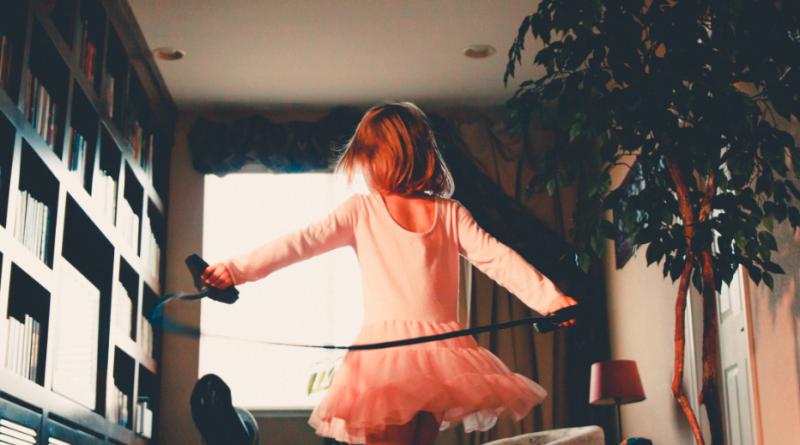Petite fille déguisée en danseuse en train de faire de la corde à sauter